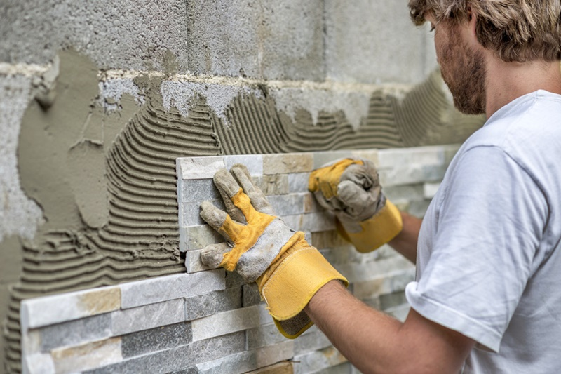 Man pressing an ornamental tile into a glue on a wall